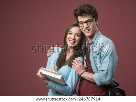 Cheerful smiling students with textbooks hanging out together - stock photo