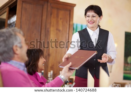 cheerful smiling waitress passing the menu to guest - stock photo