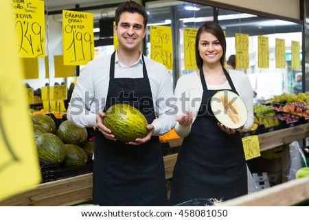 Cheerful smiling woman and man in aprons selling fresh melons on market - stock photo