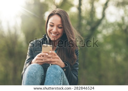 Cheerful smiling woman texting with her mobile phone and relaxing in nature