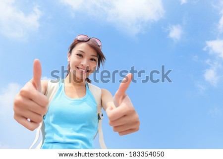 Cheerful smiling woman tourist showing thumbs up success sign with sky background - stock photo