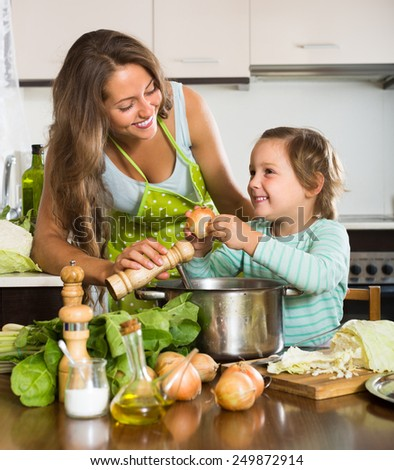 Cheerful smiling woman with little daughter cooking with vegetables at home kitchen  - stock photo