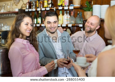Cheerful smiling young adults chatting at bar with drinks. Focus on guy