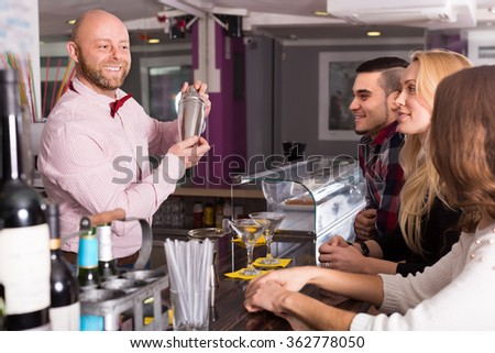 Cheerful smiling young adults hanging out in bar