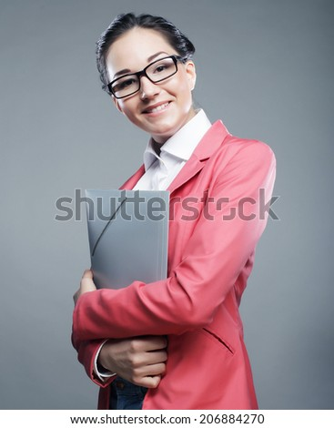 Cheerful smiling young business woman with folders, isolated over graybackground - stock photo
