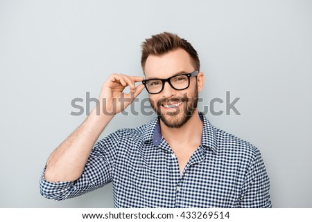 Cheerful smiling young businessman touching his glasses - stock photo