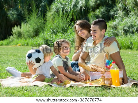 Cheerful smiling young family of four on picnic in park at summer day. Focus on girl