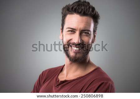 Cheerful smiling young man portrait on gray background - stock photo