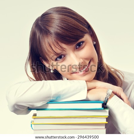 Cheerful smiling young woman in white business style clothing with textbooks - stock photo