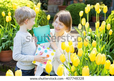 cheerful son gives her young mother present for mother's day in the park at spring time by the blooming tulips - stock photo