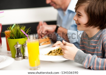 Cheerful son with his dad enjoying breakfast at restaurant. - stock photo