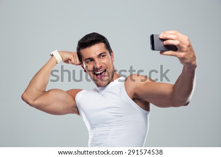 Cheerful sports man making selfie photo on smartphone over gray background