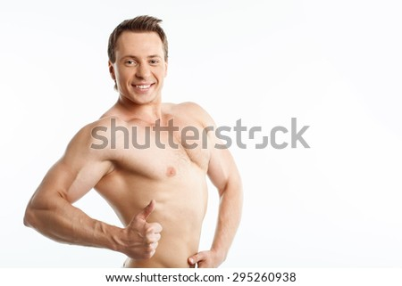 Cheerful sportsman is giving thumb up. He is standing and smiling. His torso is naked. Isolated on background and copy space in right side