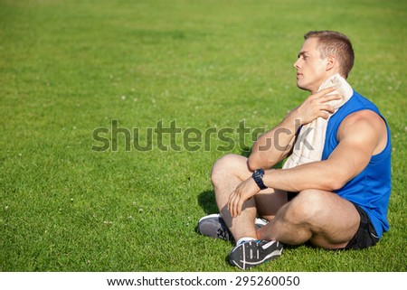 Cheerful sportsman is sitting on grass and relaxing. He is holding towel and drying his neck with it. The man is looking forward with concentration. There is copy space in left side - stock photo