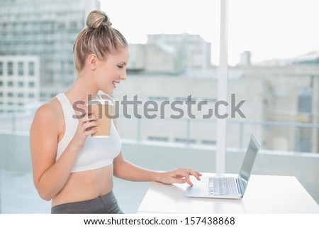 Cheerful sporty blonde using laptop holding coffee in bright room - stock photo