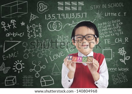 Cheerful student boy holding LEARN toy block in front of written board - stock photo