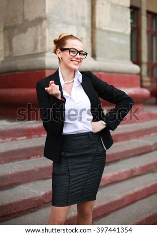 Cheerful student girl pointing a finger in a business suit on a university background - stock photo