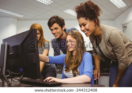 Cheerful student pointing at computer in computer room - stock photo