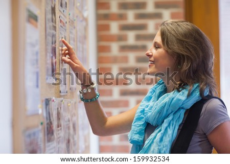 Cheerful student pointing at notice board in school - stock photo