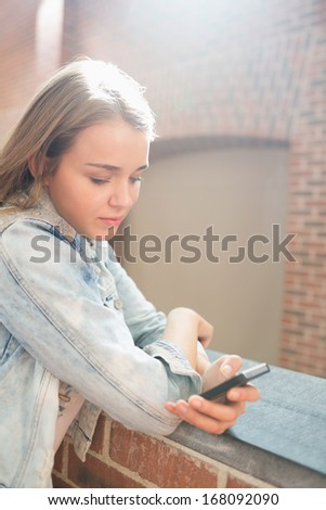 Cheerful student standing in the hall sending a text message in college