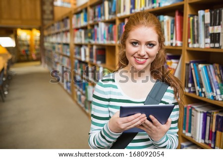 Cheerful student using tablet standing in library at the university