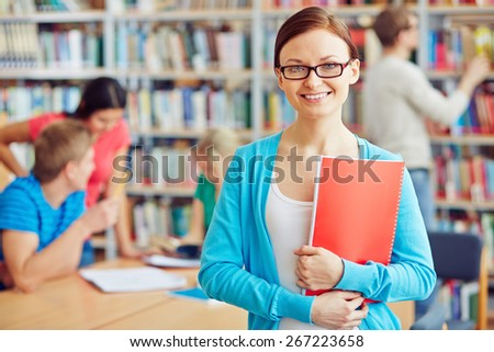 Cheerful student with copybook on background of her college friends - stock photo
