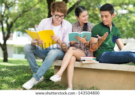 Cheerful students discussing something outside - stock photo