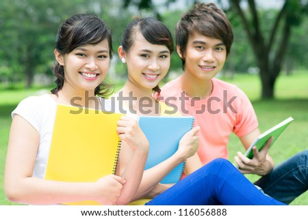 Cheerful students doing their homework outdoors - stock photo