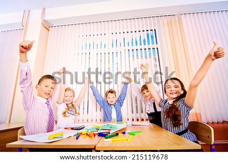 Cheerful students sit at their desks during a lesson. Education. - stock photo
