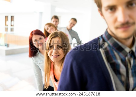 Cheerful students standing in hallway high school - stock photo