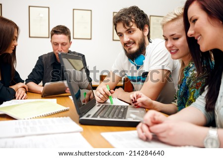 Cheerful students with laptop in a classroom - stock photo
