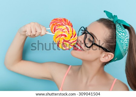 Cheerful styled woman is eating lollipop with pleasure. She is holding two candies near her face and smiling. The woman is looking at it with desire. Isolated on blue background - stock photo
