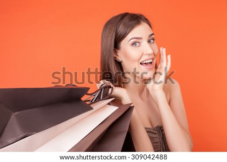 Cheerful styled woman wants to buy everything. She is standing and carrying man packets. The lady is smiling and raising her arm to her face with amazement. Isolated on orange background - stock photo