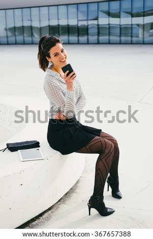 Cheerful stylish business professional woman texting or reading message on smartphone and sitting outside from modern corporate building. Relaxed young sexy businesswoman on a job rest. - stock photo