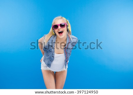 Cheerful stylish female teenager posing over blue background - stock photo