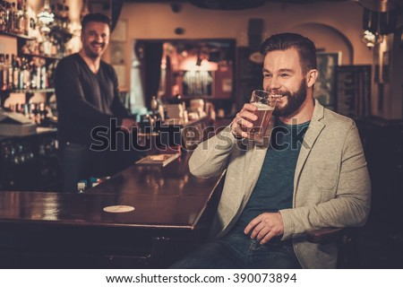 Cheerful stylish man having fun watching a football game on TV and drinking draft beer at bar counter in pub. - stock photo