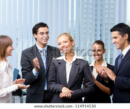Cheerful successful business woman with applauding team - stock photo