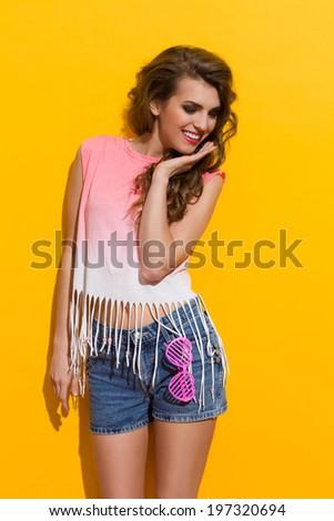 Cheerful summer girl. Beautiful young woman posing. Three quarter length studio shot on yellow background. - stock photo