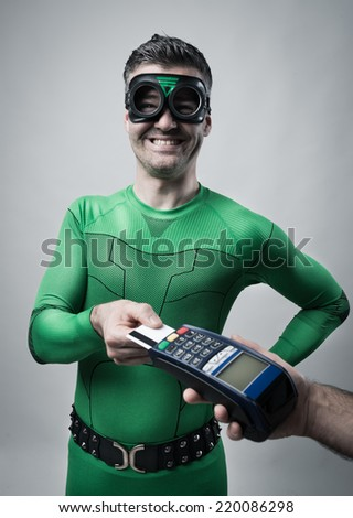 Cheerful superhero inserting a credit card into a payment terminal. - stock photo