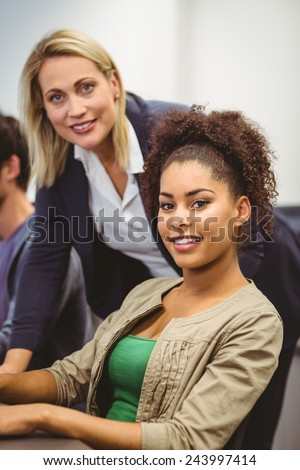 Cheerful teacher and student looking at camera in the computer room - stock photo