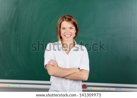 Cheerful teacher posing with arms crossed in front of blackboard