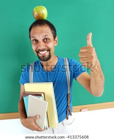 Cheerful teacher with an apple on her head, showing thumbs up. Photo adult teacher near blackboard, education concept - stock photo