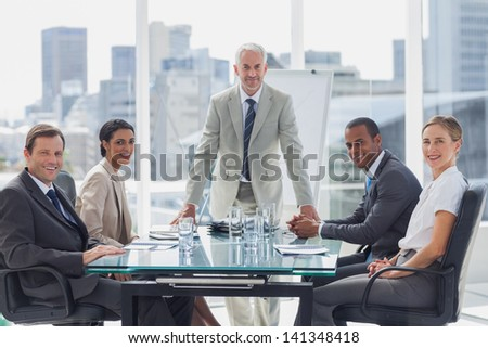 Cheerful team of business people in the meeting room with the boss standing in the middle - stock photo