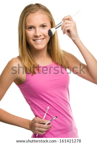 Cheerful teen girl is applying makeup using brush, isolated over white - stock photo