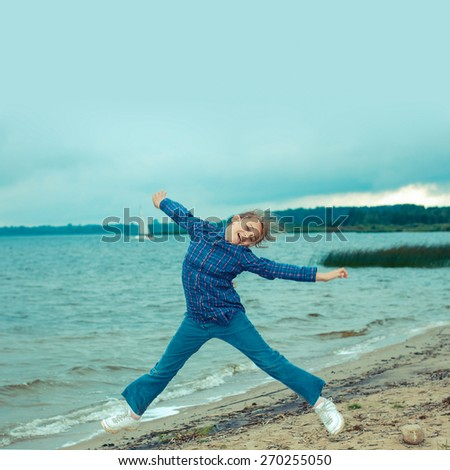 cheerful teen girl jumping on the beach in cloudy windy weather - stock photo