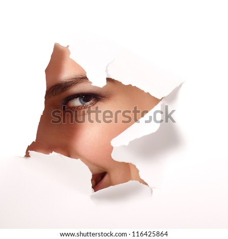 cheerful teen girl peeping surprised through hole of white paper - stock photo