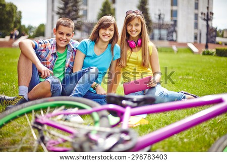 Cheerful teenage friends relaxing on green lawn in summer