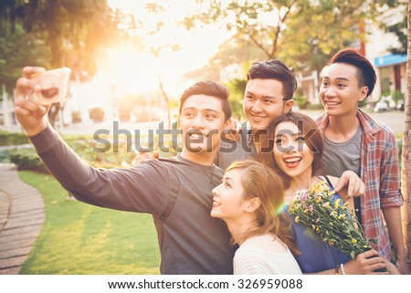 Cheerful teenage friends taking selfie against sunset - stock photo