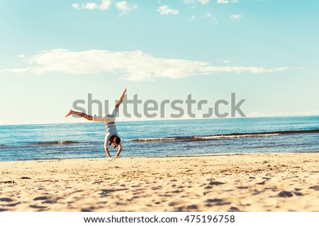 Cheerful teenage girl doing cartwheel on the beach sand on blue cloudy sky background. Vibrant multicolored horizontal outdoor summertime image with vintage filter. Copy space. Latvia.