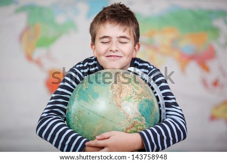 Cheerful teenage schoolboy hugging the globe in geography class. - stock photo